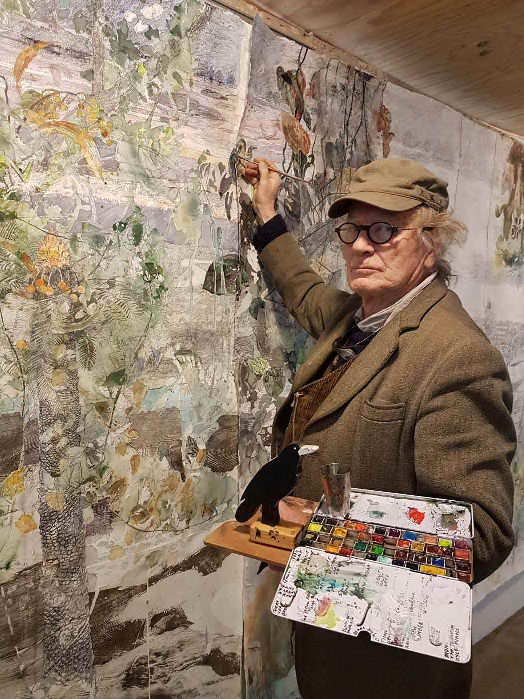 The artist stands in front of a large artwork with his brush raised to the paper and a palette in the other hand.