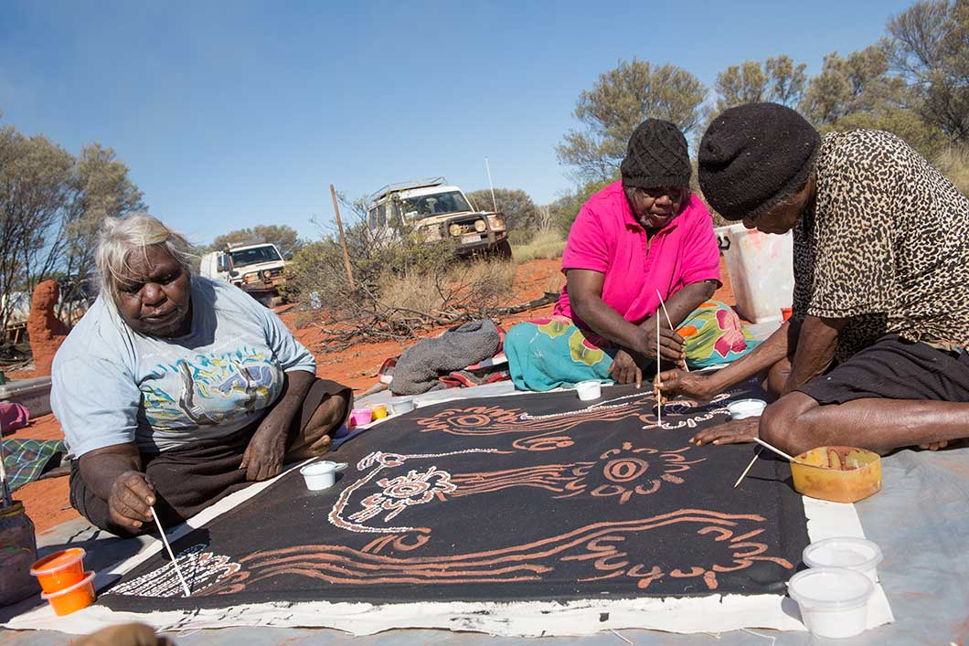 Three artists seated on the ground working on a large painting - click to view larger image