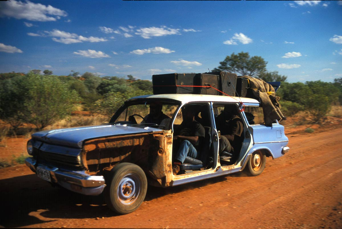 An EJ Holden with passengers travelling on a dirt road. - click to view larger image