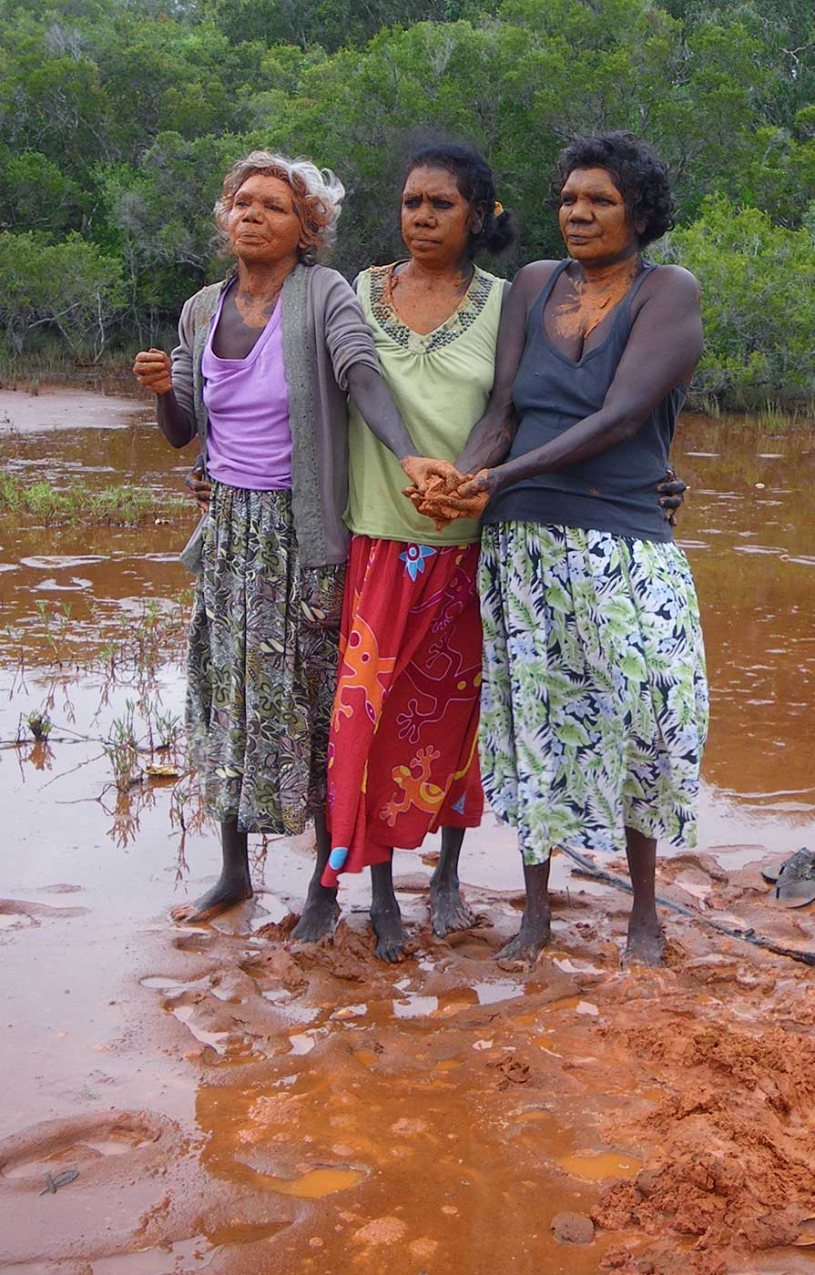 Three ladies in stand bare-footed in red clay. Their hands and faces are painted with clay. - click to view larger image
