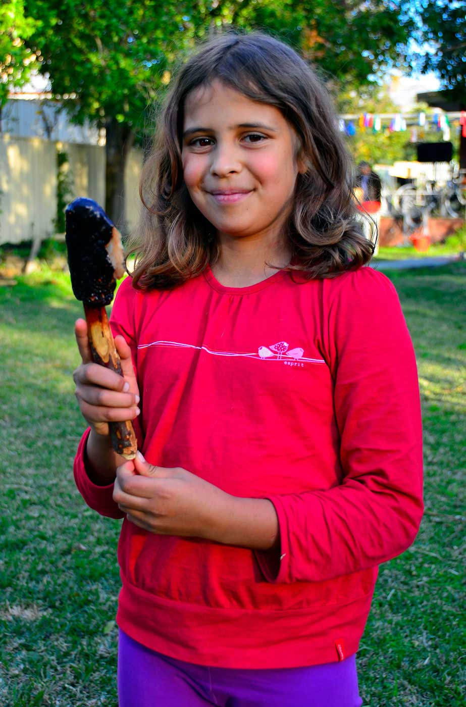 Young girl in a red shirt holding a kodj (axe) - click to view larger image