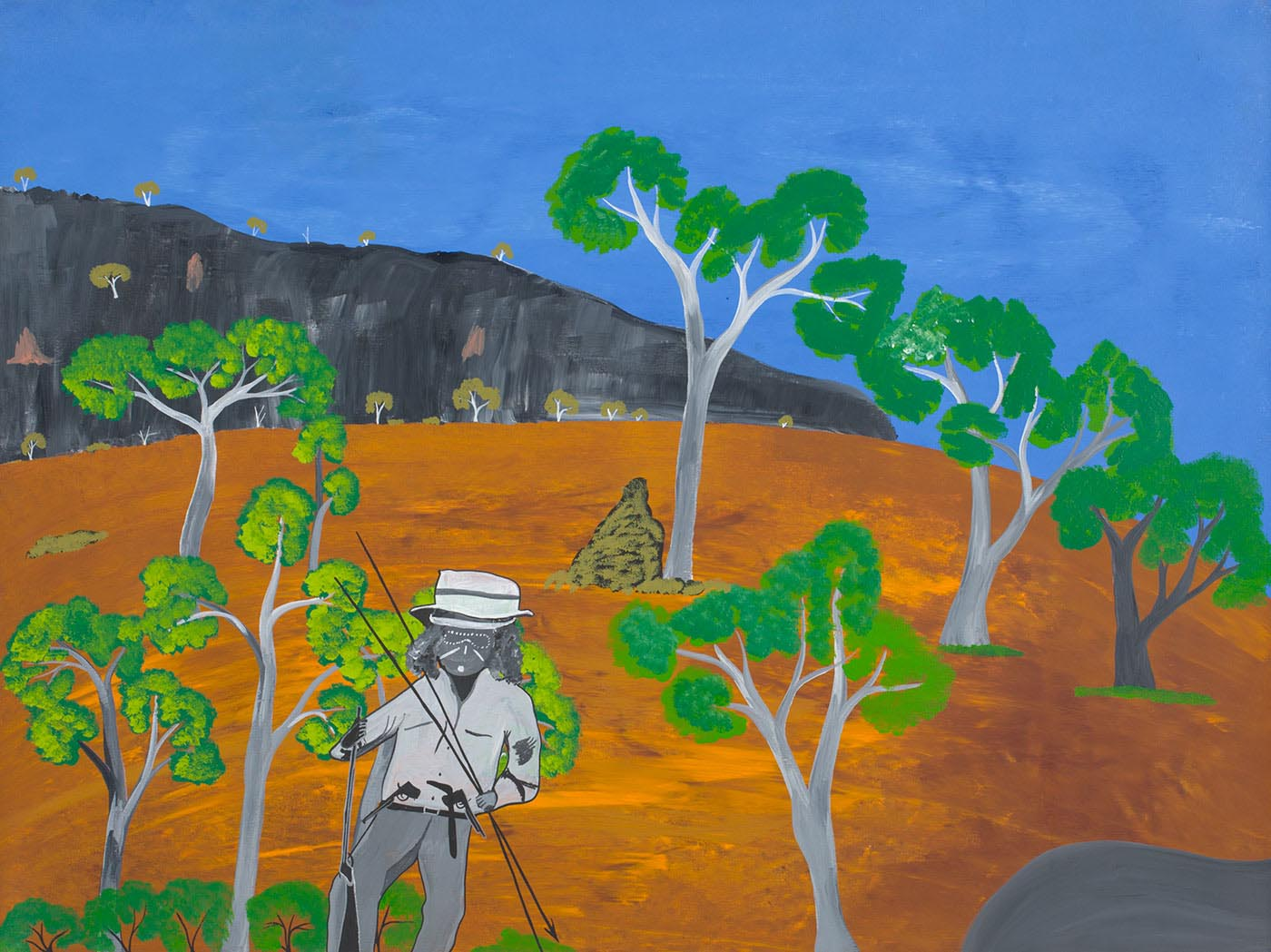 An acrylic painting on canvas depicting an Aboriginal man standing amidst a landscape. The man is wearing a white, grey and black brimmed hat, with a light grey shirt and dark grey pants. He is also holding spears in both hands. The landscape features a blue sky and grey black mountains with trees in the background. The foreground consists of orange brown grassland with trees that are green, grey and white in colour. Also to the front right side of the painting is a grey rock.