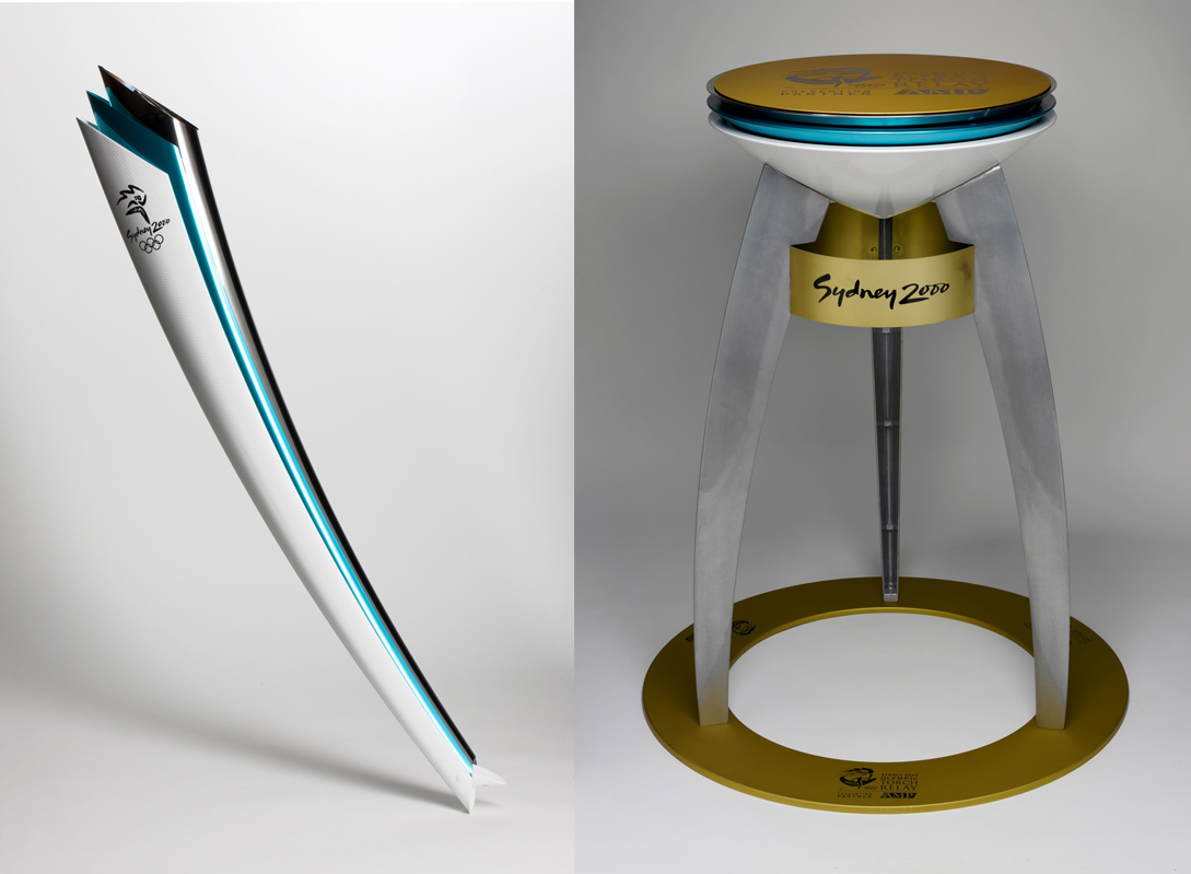 On the left is an image of an Olympic relay torch coloured silver, aqua blue and white, with a silver logo on each side. On the right is an image of an Olympic community metal cauldron with a white, blue and silver coloured cone shaped dish supported by three curved legs. The legs are attached to a yellow circular base. 'Sydney 2000' is printed three times in black on a yellow band under the base of the dish. 'SYDNEY 2000 / OLYMPIC TORCH / RELAY / PRESENTING PARTNER / AMP' with Sydney 2000 logo and Olympic rings is repeated three times on base and printed on top. - click to view larger image