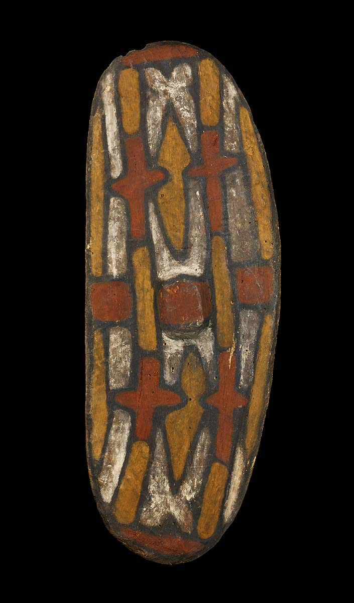 An oval, curved wooden shield with and abstract design of interlocking shapes in red, white and yellow ochre running along its length, all outlined in black. There are four cross shapes and two lozenge shapes. - click to view larger image