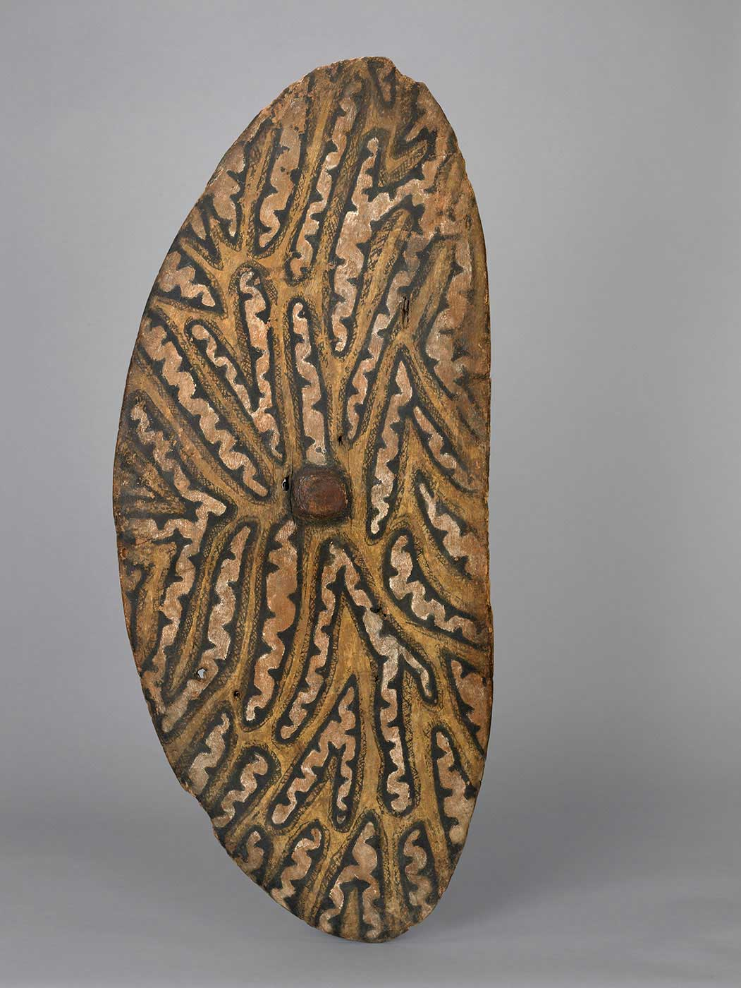 Ellipse-shaped bark shield featuring a yellow ochre design and a reddish-brown circle in the centre. - click to view larger image