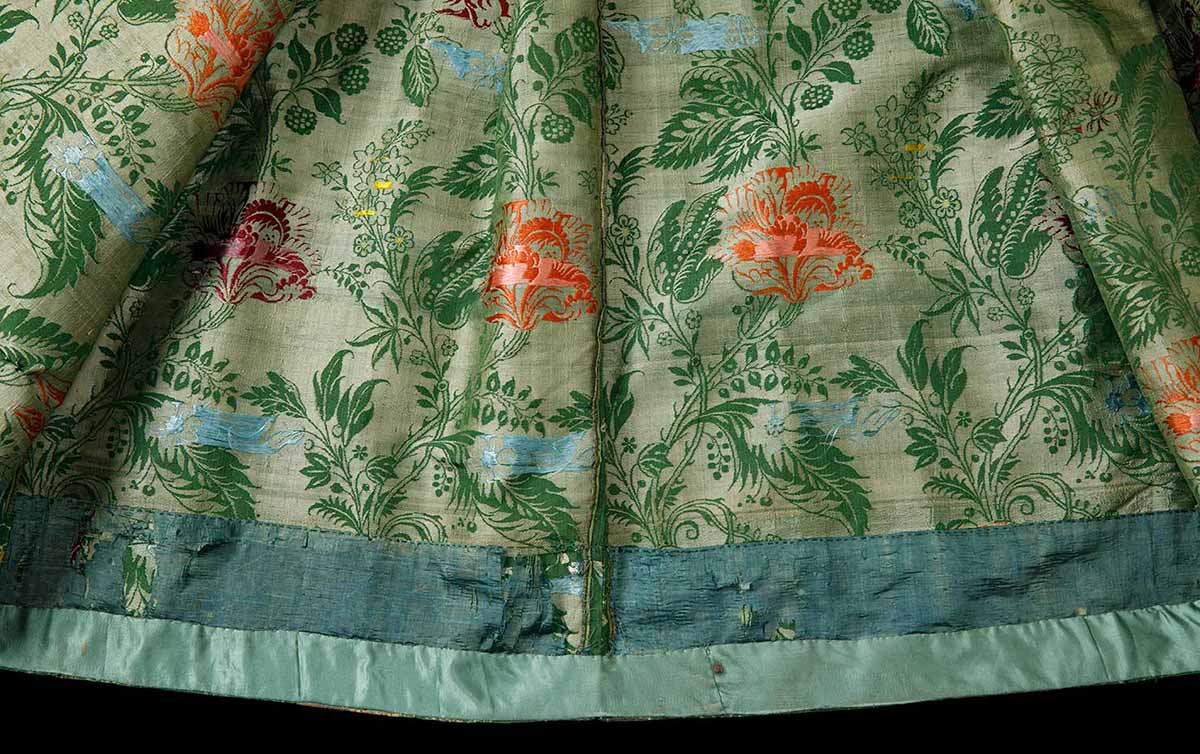 A detail image of the hem of a green and floral dress. - click to view larger image