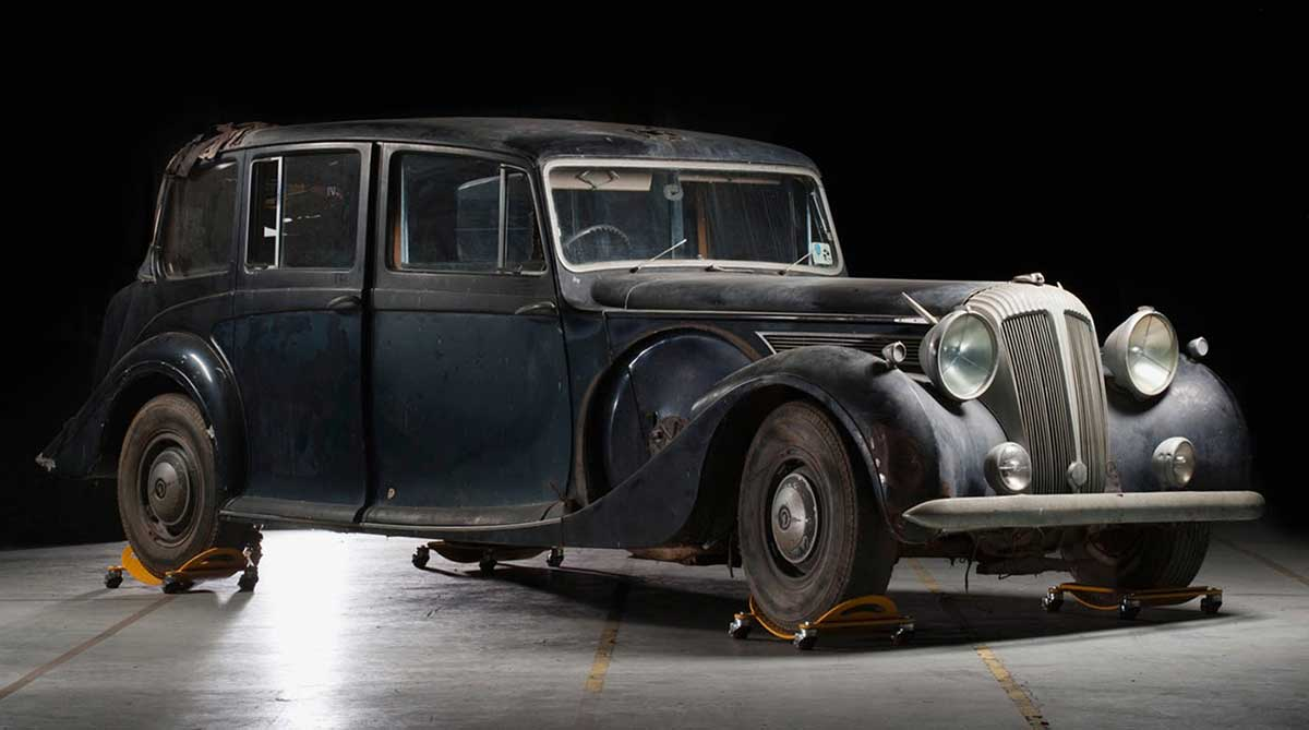 A long, sedan-style car with faded black paint, on jacks in an exhibition space. - click to view larger image