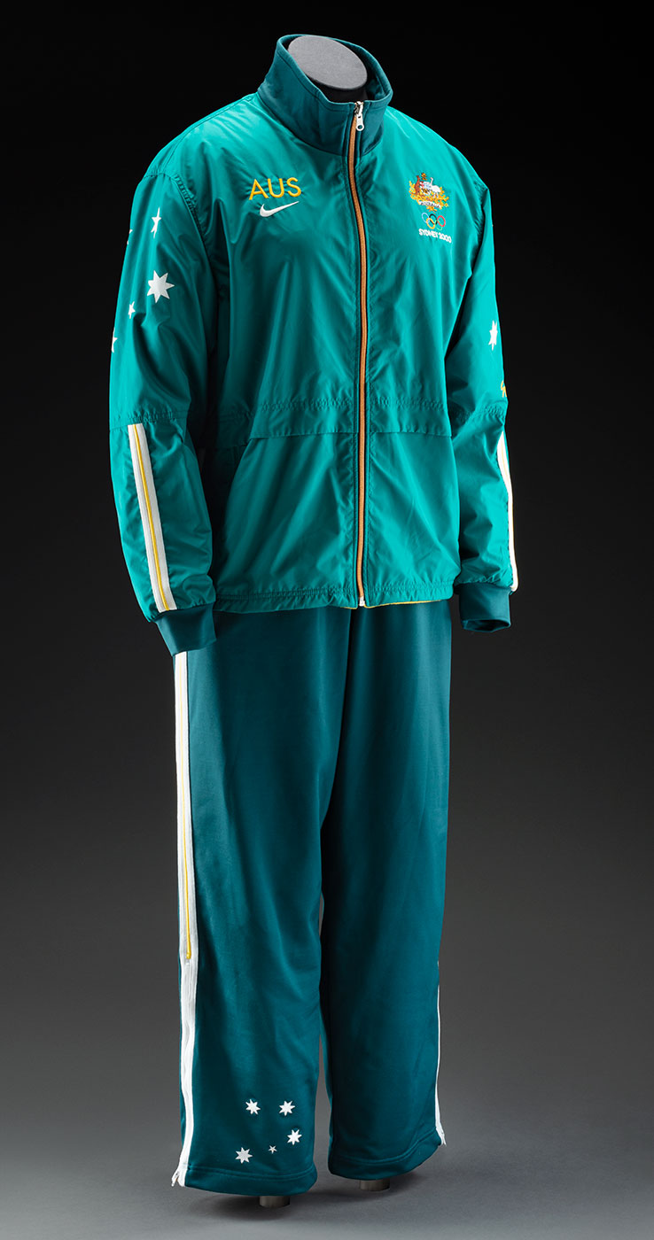 Dark green tracksuit top and pants, with gold trim, on a mannequin. - click to view larger image