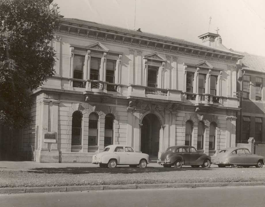 black and white photo of two-storey 19th-century building with three mid- 20th century cars parked in front of it. - click to view larger image