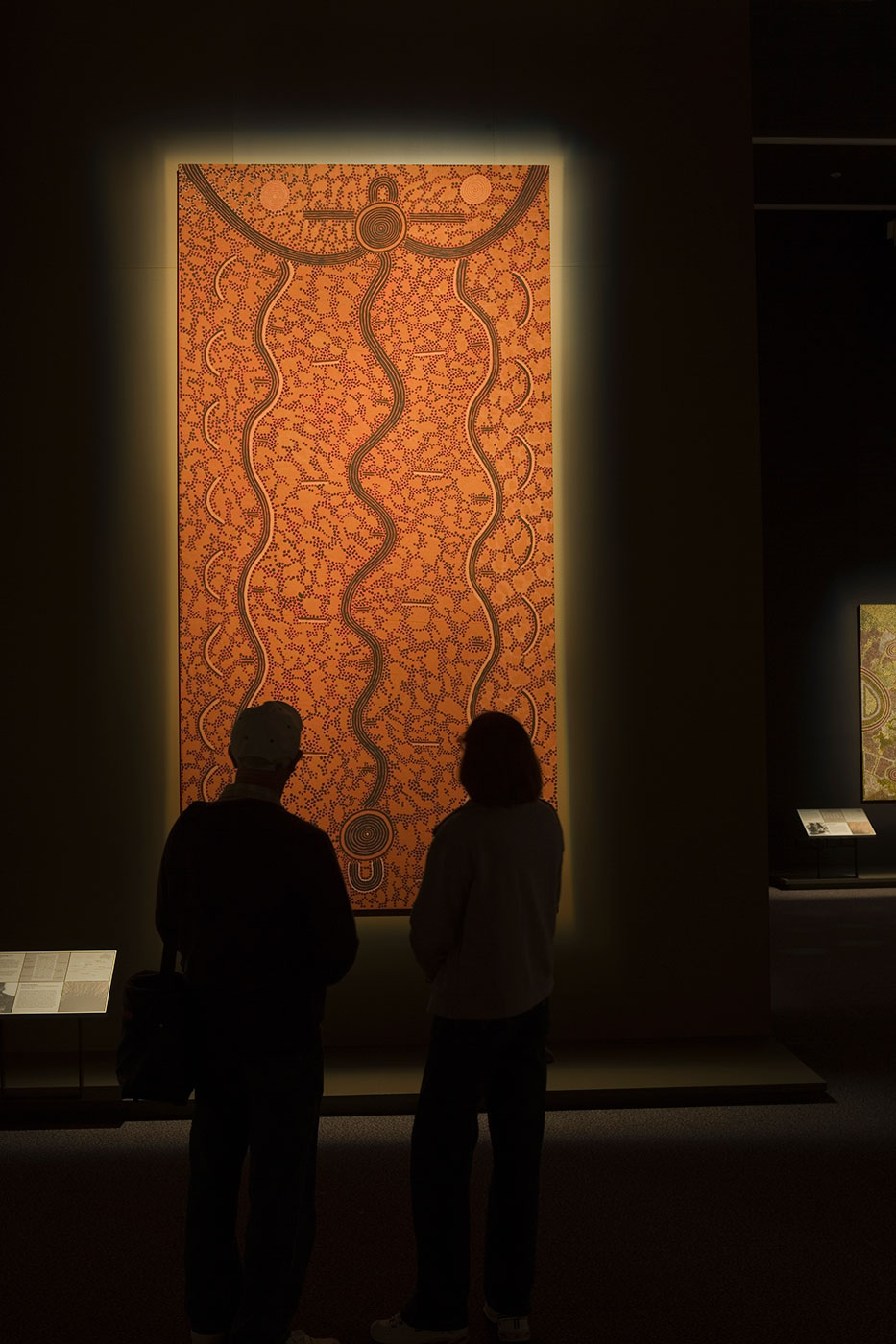 Rear silhouette of two visitors looking at large canvas. - click to view larger image