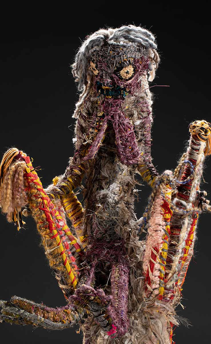 A detail image of a human like figure seated at the top of a tree sculpture. The figure features, hair, a face, breasts, arms, fingers, legs and toes. The sculpture is made of various plant-based and synthetic materials. - click to view larger image