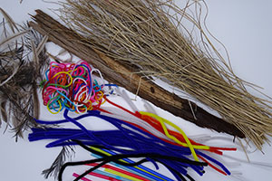 A collection of craft materials are laid out on a white background. Some materials are plant-based and have the appearance of wood and brown string-like material, and others are a mixed coloured ball of wool and a pile of blue, black, white, orange and yellow pipe-cleaners.