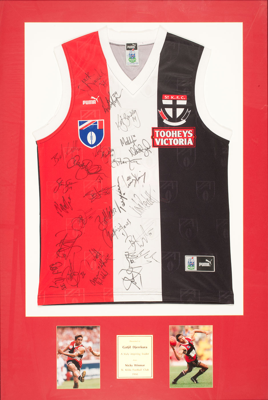 A framed red, white and black sleeveless top with V-neck and logos on both breasts. It has various signatures in black across the front. Two small colour photographs of a footballer in play appear underneath, with a central gold-coloured plaque which reads 'Presented to / Gatjil Djerrkura / A truly inspiring leader / from / Nicky Winmar / St Kilda Football Club / 1998'. - click to view larger image