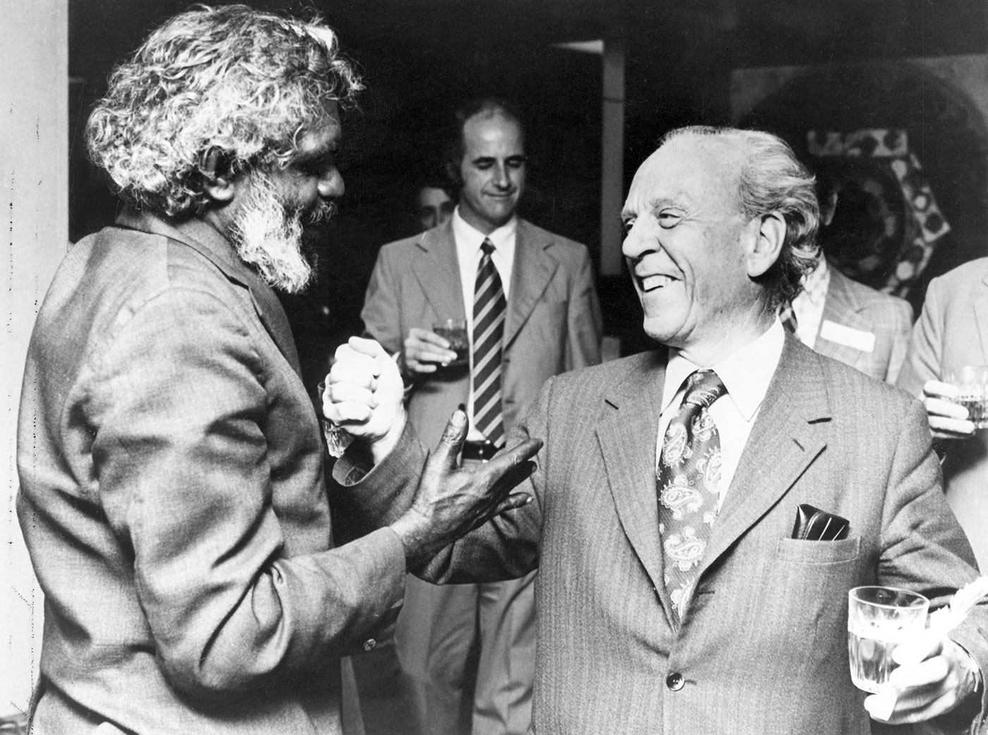 Black and white photo showing the side profile of a man at left. He has whitish-grey curly hair and a beard and extends his right hands towards another man, who has his left hand raised and holds a glass in the right. The man on the right wears a striped suit and paisley tie and is smiling.