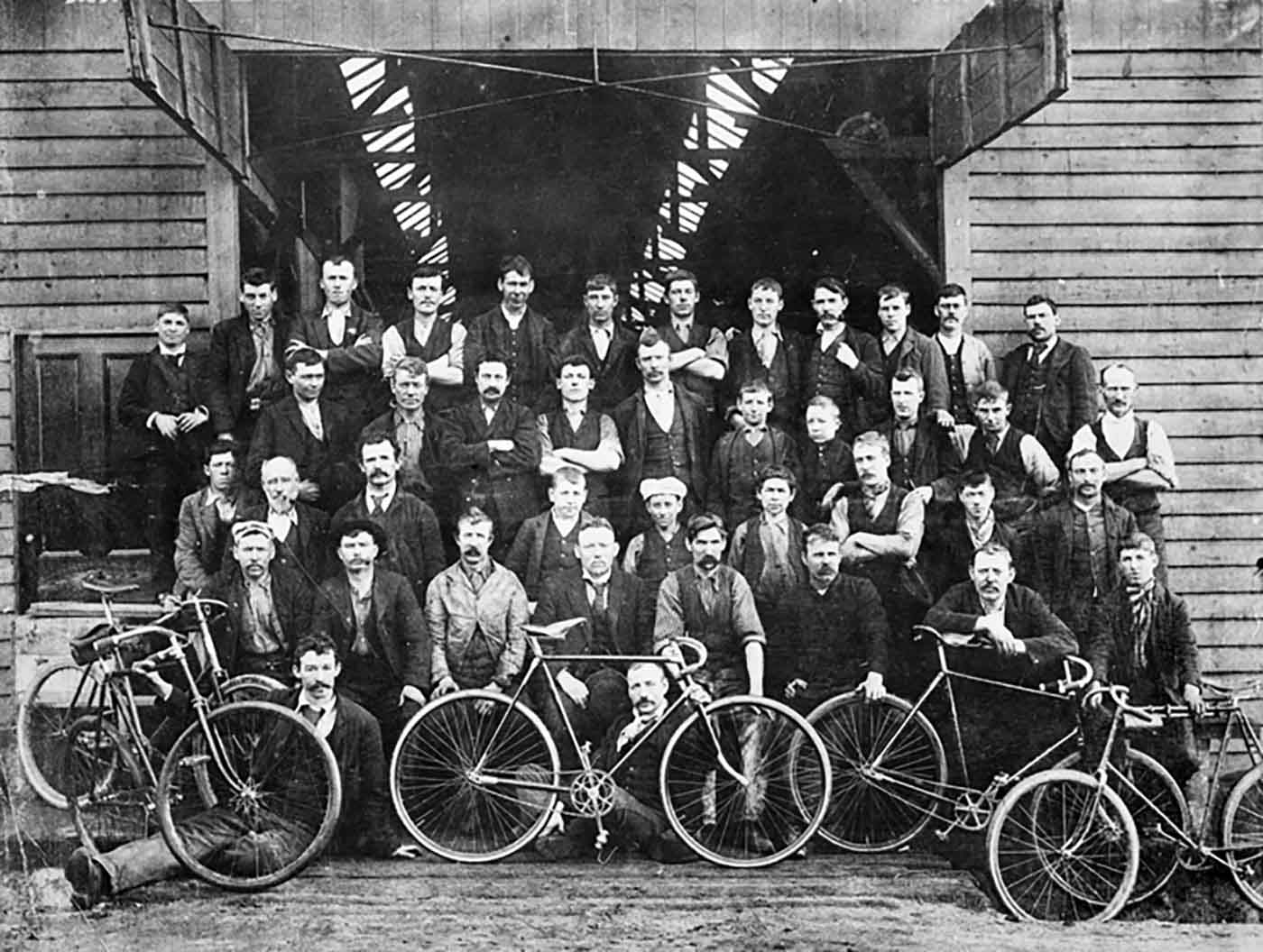 Black and white photo of a group of men posing in front of a factory building.