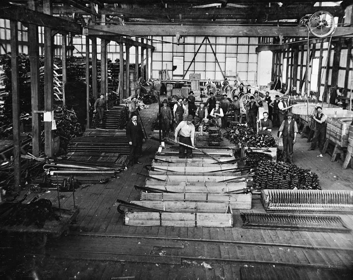 A black and white photo of several man inside a factory in 1918 packing harvester combs, comb teeth, wheels and other parts into shipping crates. - click to view larger image