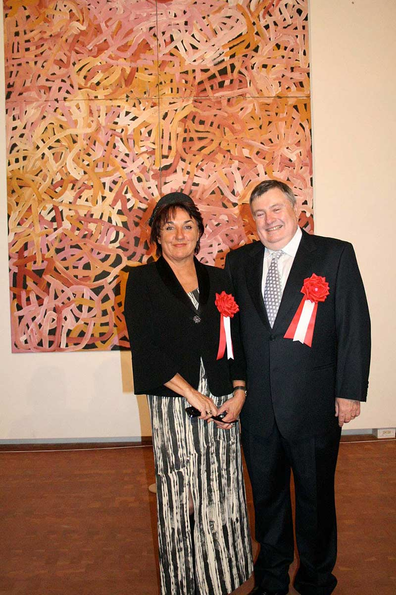 A man and a woman in formal wear standing in front of a large painting. - click to view larger image