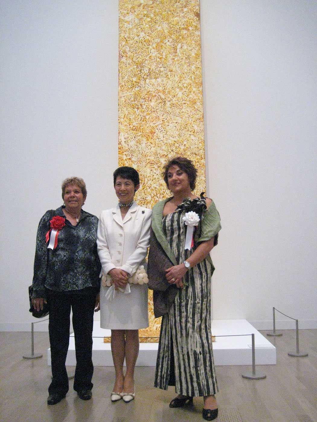 Three women standing in front of a painting. - click to view larger image