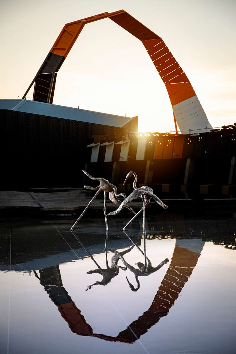 A sunset photo featuring a bronze sculpture consisting of two separate brolga figures. The display is set in a large body of water with the National Museum of Australia building and its bright swooping loop behind it which is reflected in the water. - click to view larger image