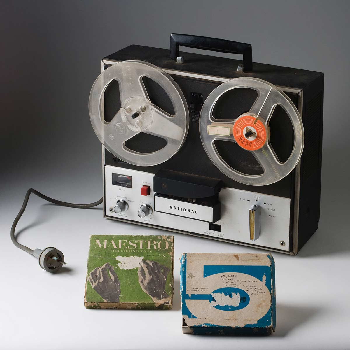 A 'NATIONAL' reel to reel tape recorder made from black plastic and silver coloured metal, with a power cable, a handle at the top, and a removable black plastic cover. - click to view larger image