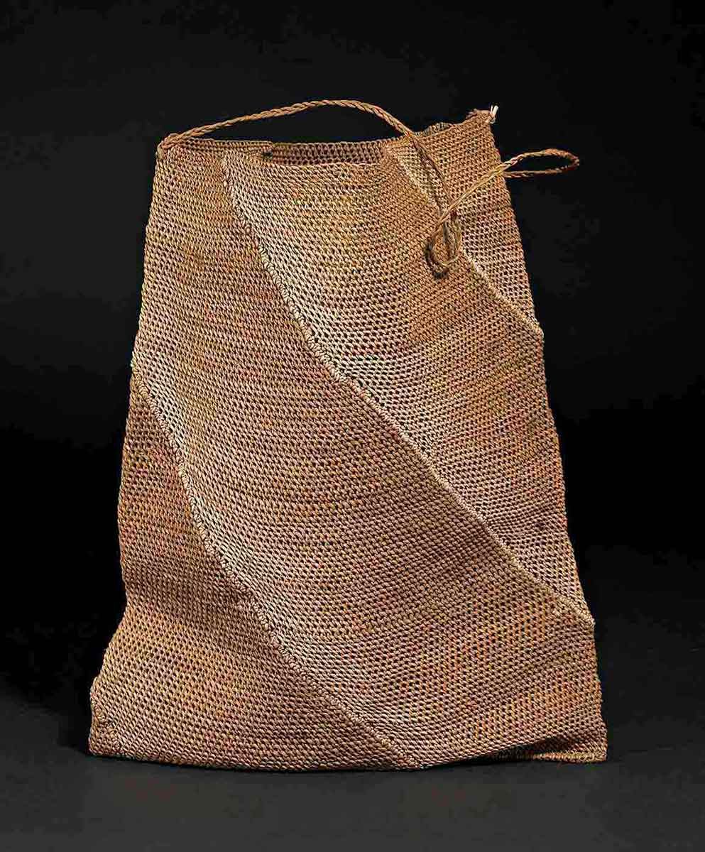 A pale-brown woven bag with a handle made of vegetable fibre. - click to view larger image