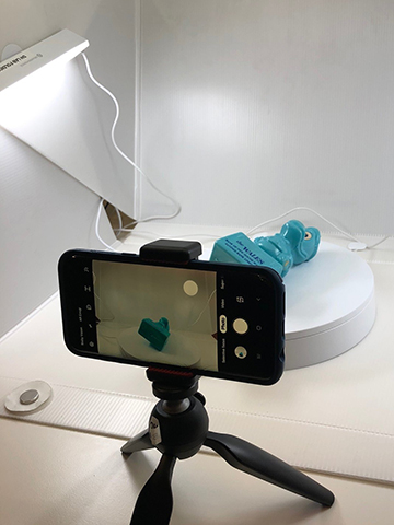 A photograph of a mini tripod and mobile phone positioned for photographing a small blue object inside a lightbox.