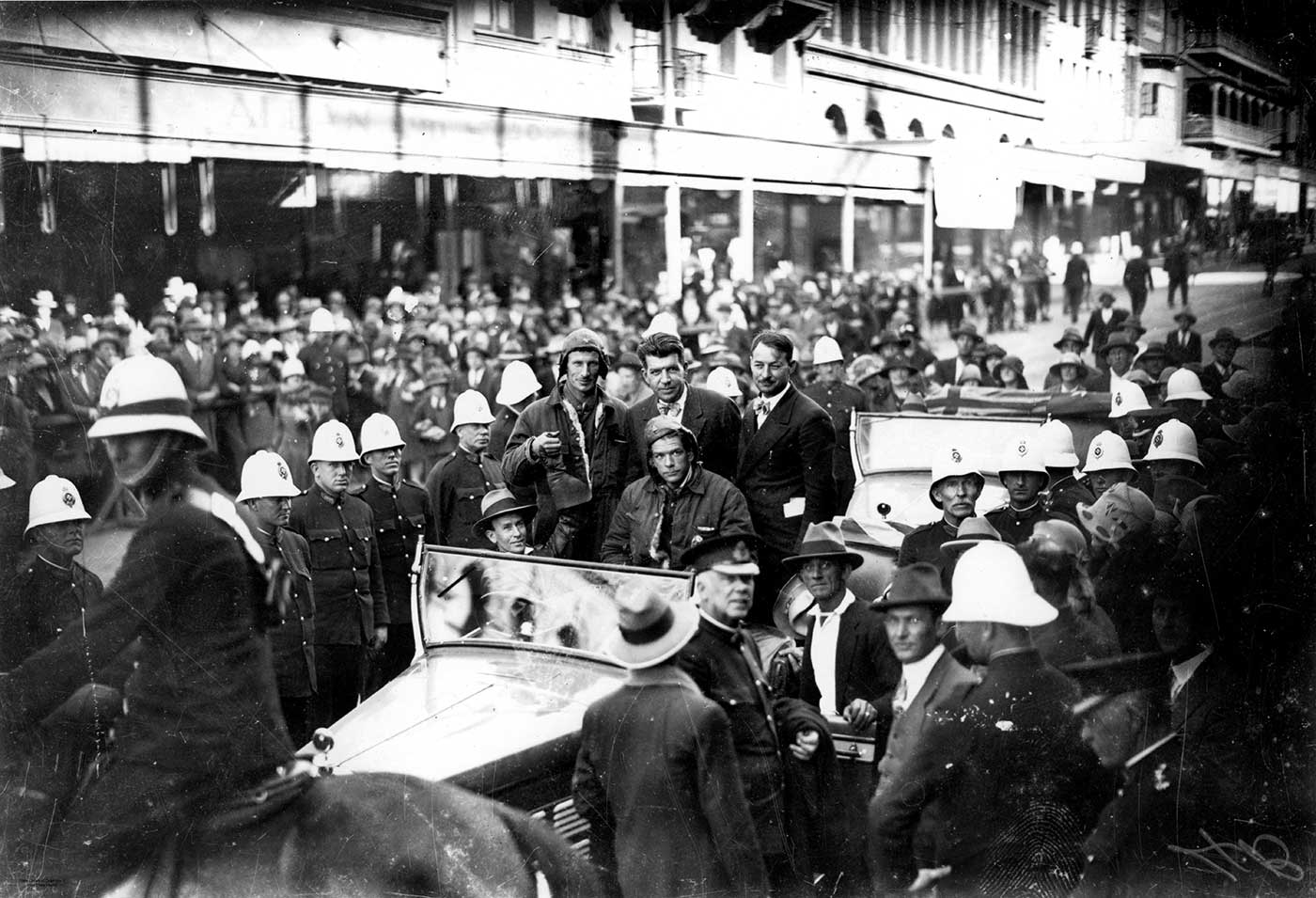 The crew of the Southern Cross in a car surrounded by people and policemen