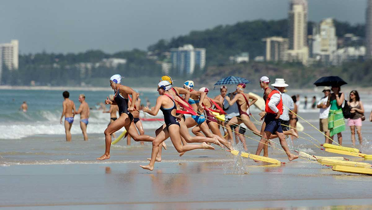Female lifesavers running into the surf at the start of a race at the Australian Surf Life Saving Championships, Kurrawa, Queensland, 2006.