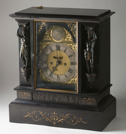 A colour photograph of an ornate clock. The clock has a dark coloured body with decorative features. Small figures can be seen at either side of the clockface. The clockface itself is surrounded by elaborate gold inlay. The base of the clock body has a decorative motif on the side closest to the camera. The entire clock sits on a neutral grey background, suggesting that it has been photographed in a studio setting.
