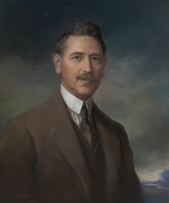 A portrait painting of a man wearing a brown suit and vest, white shirt with a high collar and a dark tie. He has dark neatly combed hair and a moustache. He is visible from the lower chest up. His torso faces toward the right of the painting and he has his head turned toward the viewer. His expression is one of calm and confidence. The background of the portrait is a cloudscape, with clouds in dark tones and a small glimpse of blue sky in the lower right hand corner.