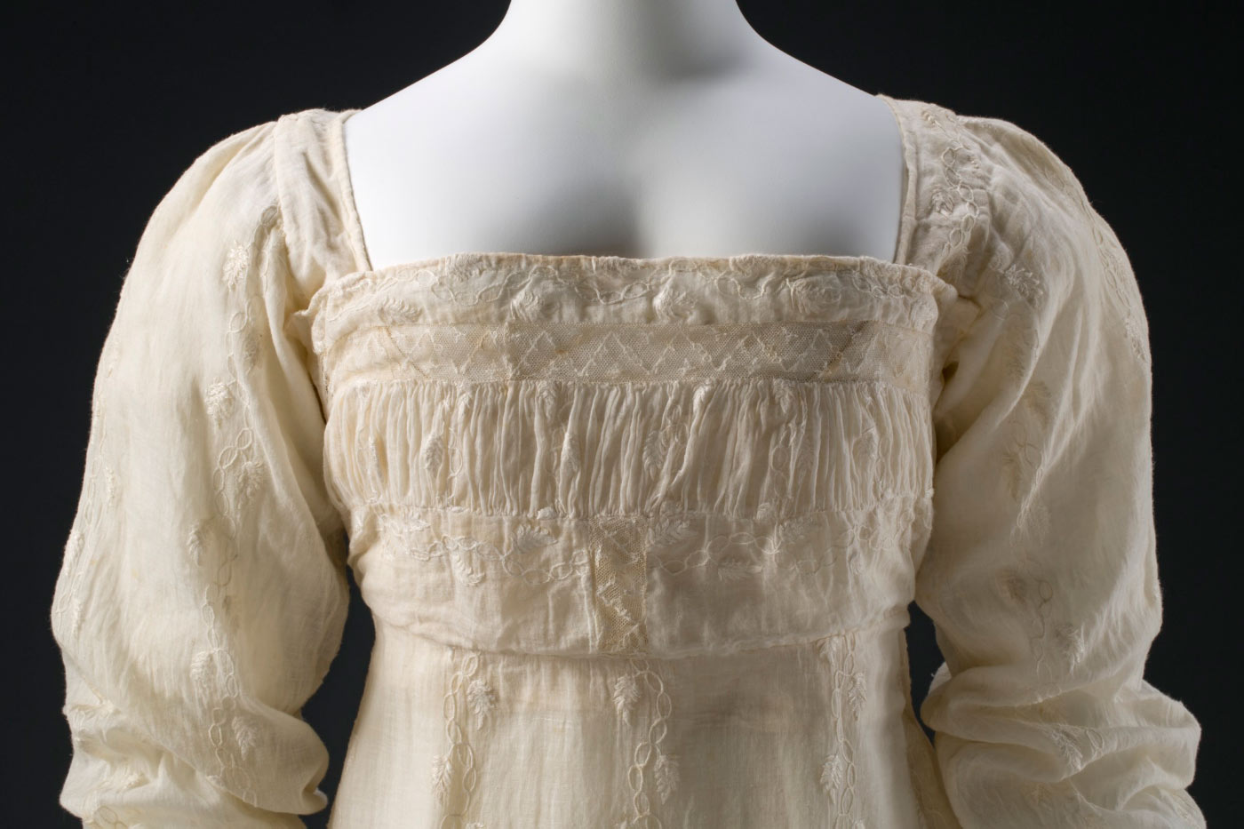 Bodice featuring a shirred band, which has an insertion of machine-embroidered net (a later alteration) at the top.