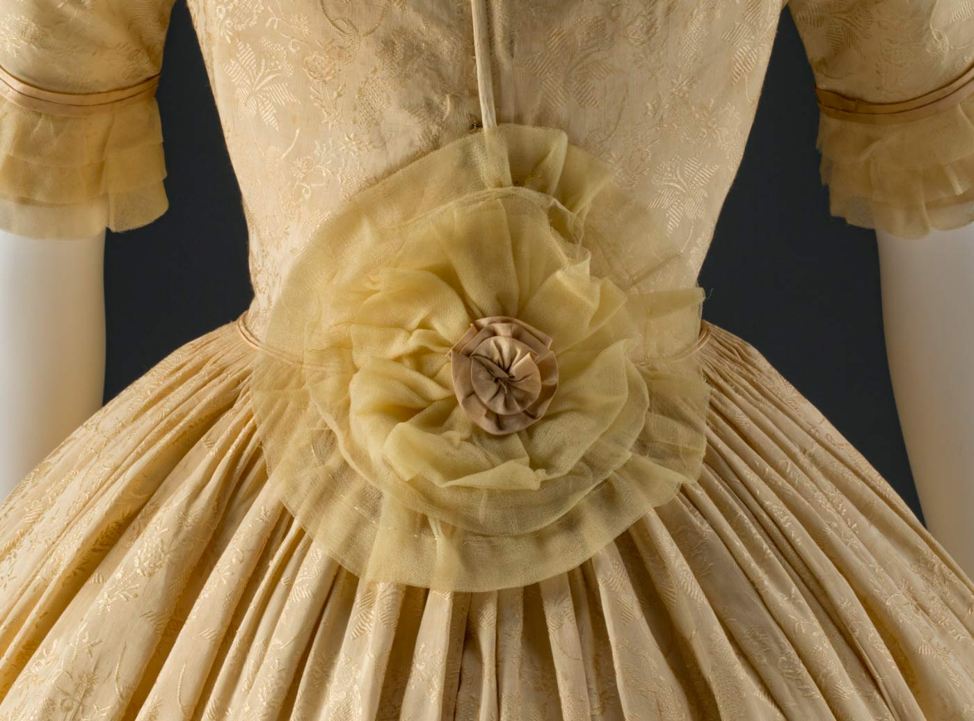 A large gold silk chiffon and satin rosette at the back of the dress conceals alterations to enlarge the waistline.