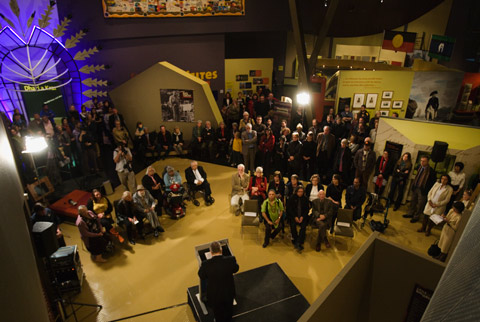 A colour photograph of an exhibition launch in a museum. The photograph has been taken looking down upon the launch, in a 'bird's eye' view. In the foreground of the photograph is a lectern on a small stage. A man stands at the lectern, with his back to the camera. In front of him are two groups of what appear to be official guests for the launch. They all sit on seats. Behind them stand many more people. In the background can be seen what appears to be an exhibition.