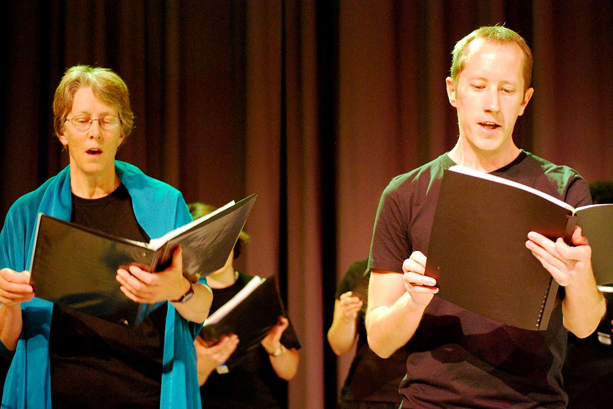 A woman and man singing alongside a choir on a stage. - click to view larger image