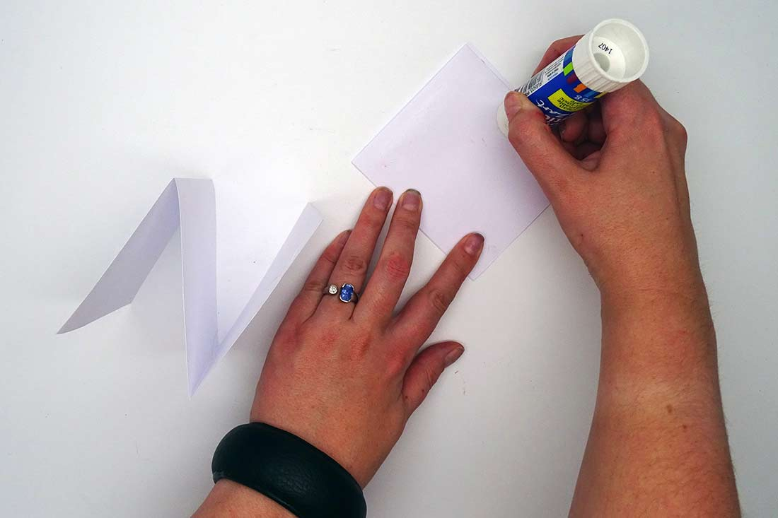 Two hands applying glue to paper - click to view larger image