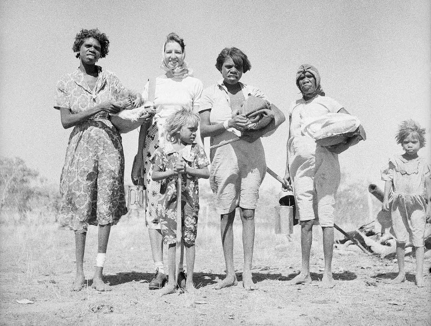 A black and white photo of a group of four women, two children and two babies.