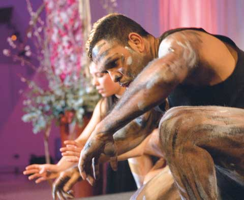 Dancers Ella Havelka and Sani Townson. Townson, at the front of the image, has paint on his arms, legs and face. Both dancers are crouched towards the ground, with arms extended.