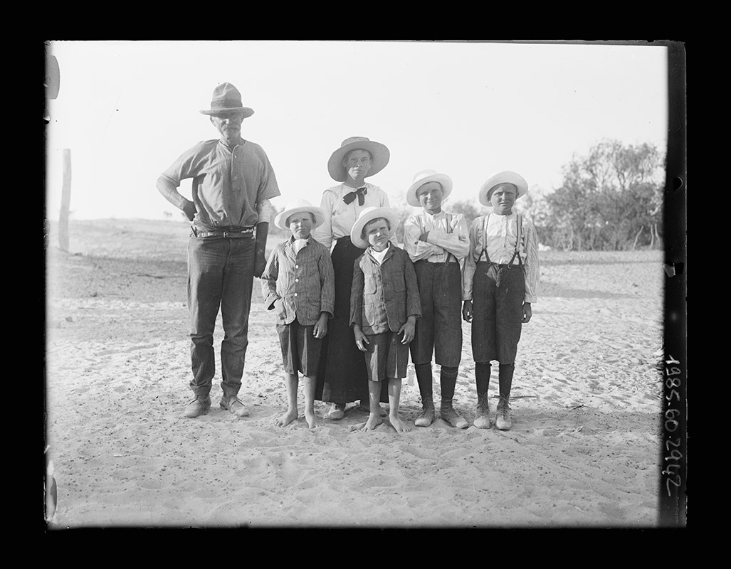 A black and white photograph of a family of six standing in a line and two smaller boys standing together in front of the woman. They are all wearing hats. The man is wearing a short-sleeved shirt tucked into long trousers with a belt. The woman is wearing a long-sleeved blouse with a bow at the collar and a full-length skirt. All the boys are wearing knee-length shorts. The two older boys are wearing long-sleeved shirts, braces and boots while the two younger boys are wearing buttoned-up jackets and are bare footed. They are standing on sandy ground with a slight rise on the left and a stand of trees on the right. - click to view larger image
