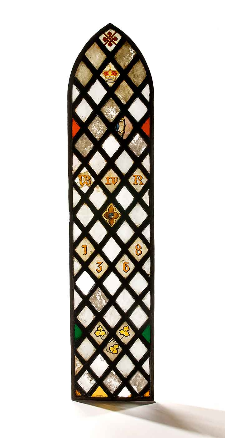 Long stained glass window featuring a crown, numbers, leaves and various shapes. - click to view larger image