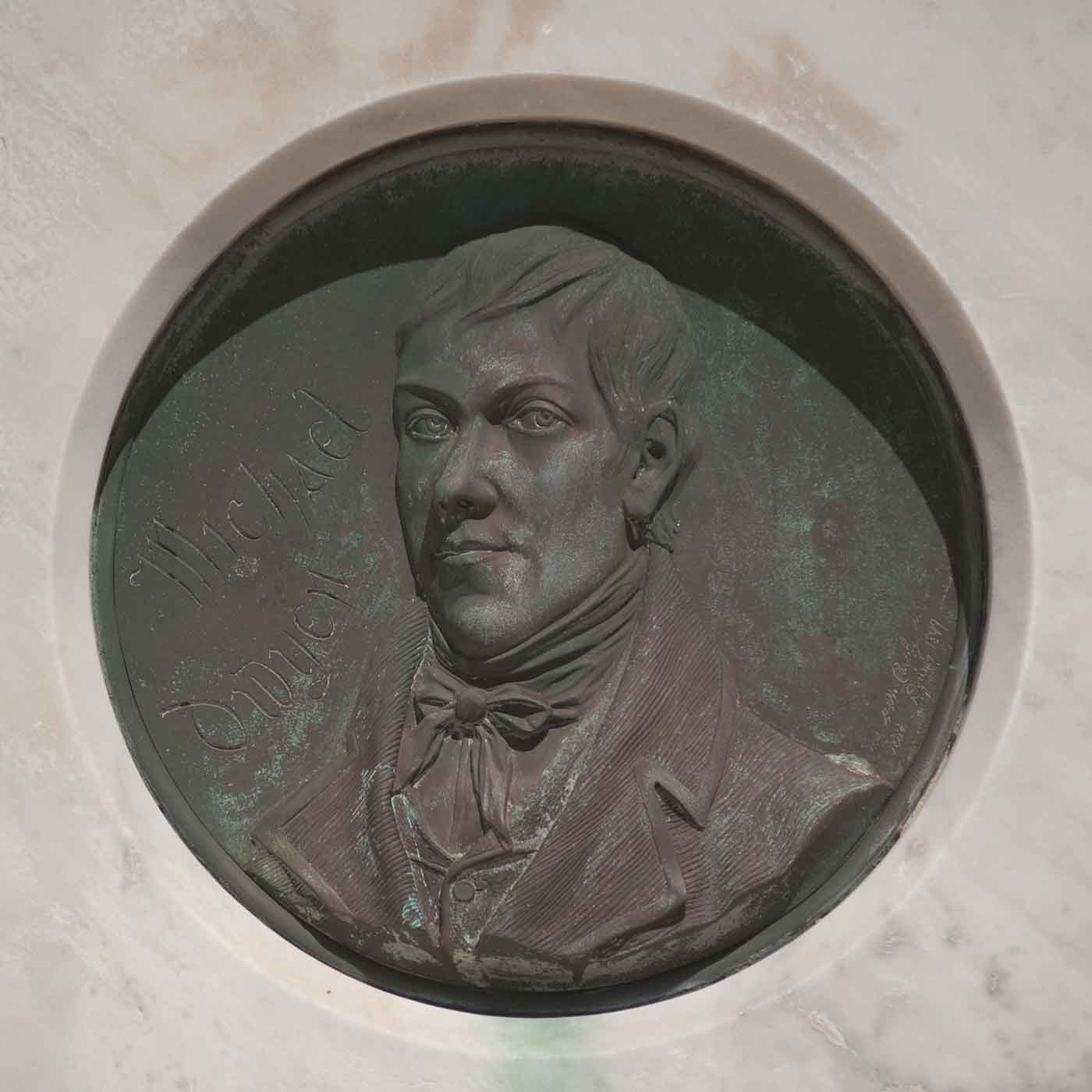 Bronze portrait of a man set in a memorial stone. - click to view larger image