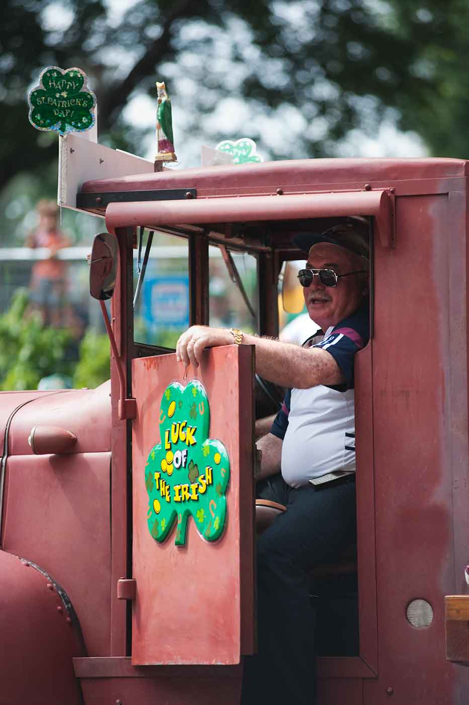 A man sits in a stationary red truck with a sign fixed to the car door of a clover and the text: LUCK OF THE IRISH. - click to view larger image