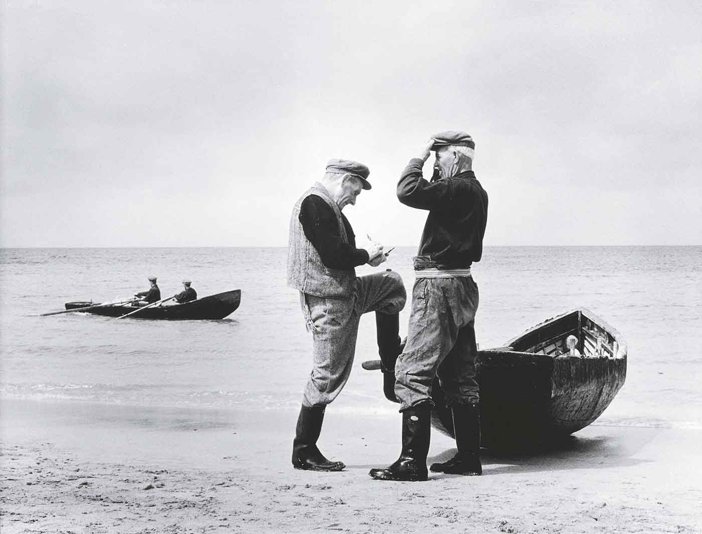 Black and white photo of two men standing beside a small boat on the shores of a sea with another boat containing two people rowing further out in the water.
