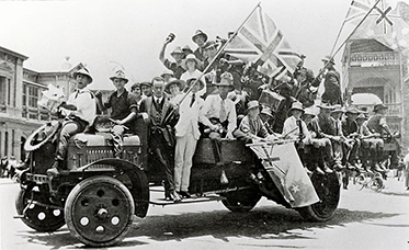 Black and white photograph of numerous people sitting and standing on a truck. Several people are waving flags.