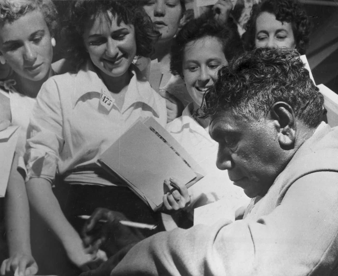 Black and white photo of a man signing autographs for a group of women.