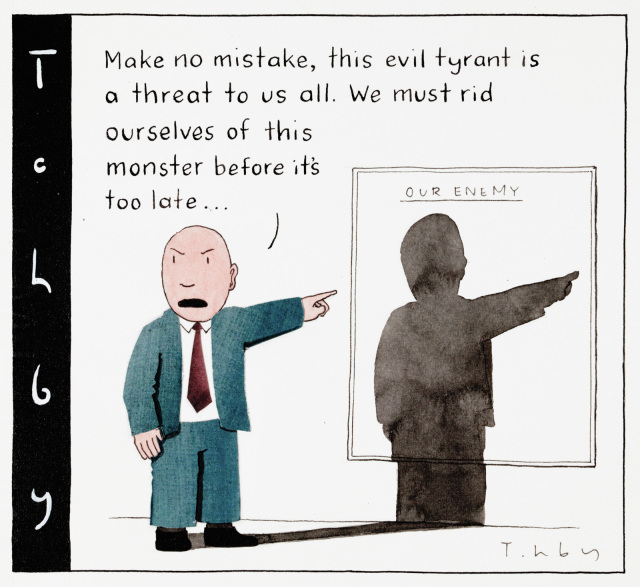 A cartoon depicting a bald man in a blue suit, pointing at a poster behind him, blank, except for the title along the top 'The Enemy'. He has an angry expression, and says 'Make no mistake, this evil tyrant is a threat to us all. Me must rid ourselves of this monster before it is too late...