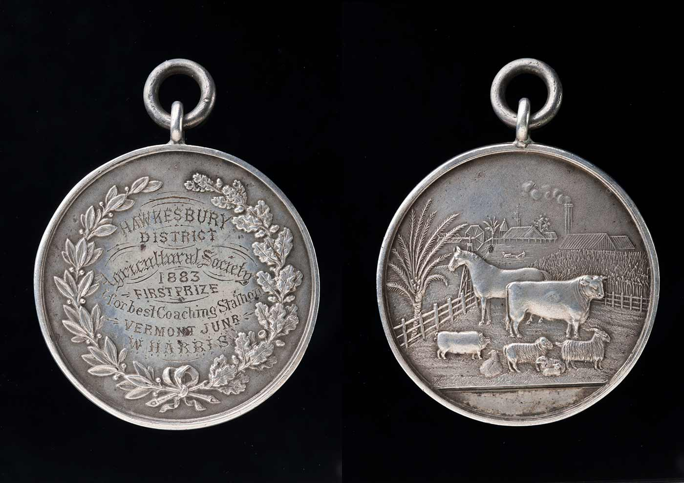 Front and back of a silver prize medal. The front has a laurel leaf border and text inscribed 'Hawkesbury District Agricultural Society, 1883, first prize for best coaching stallion, Vermont Junr, W Harris'. The back shows a rural scene with a horse, cow, pig and sheep.