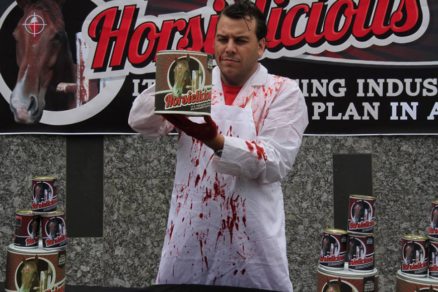 A man wearing a blood-spattered white apron holds a can of 'Horsielicious' in front of him.