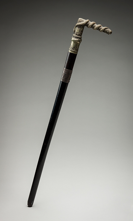 A riding crop with a silver L-shaped handle atop a black pole. - click to view larger image