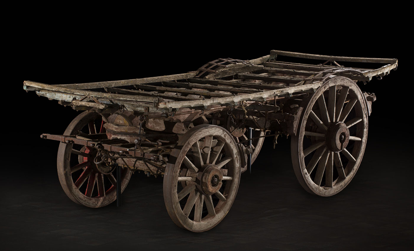 A flatbed wagonmade of timber, with larger wheels at the rear.