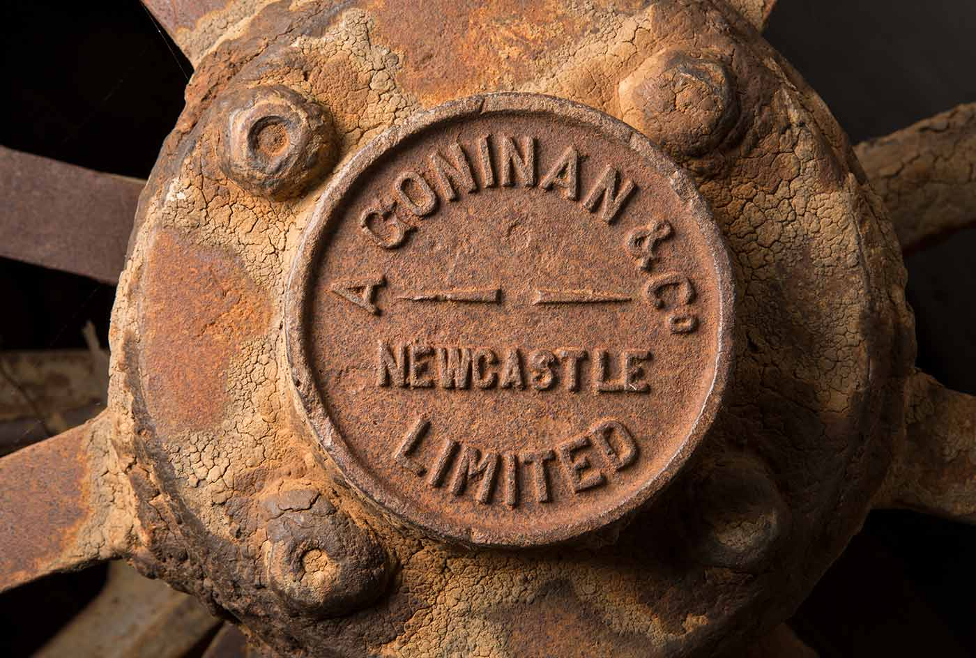 A cook's galley in the form of a metal-clad, timber and iron-framed box raised on wagon wheels. This view is of a close up of a wheel hub with the words 'A Coninan & Co, Newcastle Limited' stamped on it. - click to view larger image